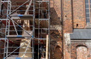 scaffolding with church spire / Scaffolding in front of the wall of a gothic brick church with the unfinished church spire