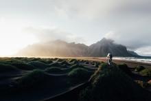 Photographer Taking Photo Of Famous Grass Hills Near Stokksnes Mountains, Iceland