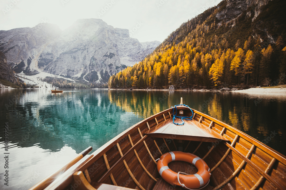 Old rowing boat on a lake in the Dolomites in fall