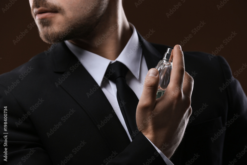 Fototapety, obrazy: Handsome man in suit using perfume on dark background, closeup