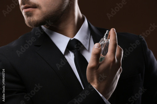 Fototapeta Handsome man in suit using perfume on dark background, closeup obraz