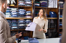 Woman Seller Assisting Man In Choosing Shirt In Men's Cloths Store