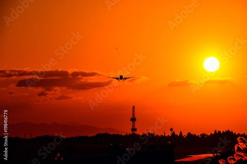 Papiers peints Orange eclat 夕日を背景に未来へ挑戦をする飛行機 An airplane challenging the future against sunset