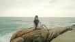 Woman spending leisure on stony beach and listening music on headphones