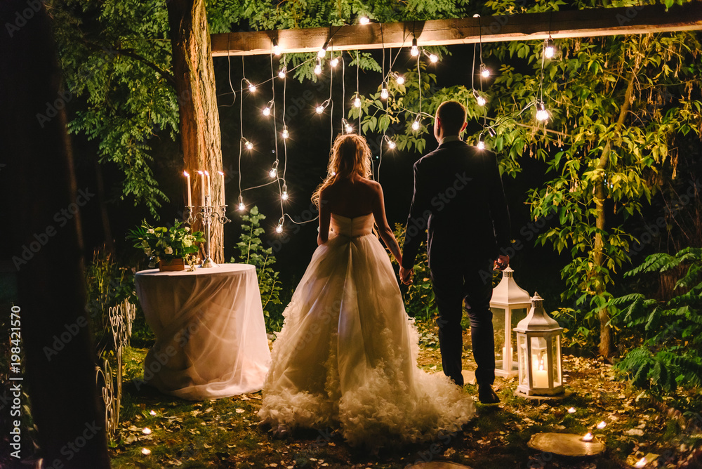 Fototapeta Night wedding ceremony with candles, lanterns and lamps on tree. Bride and groom holding hands on background of baulb lights, back view. Beautiful young couple standing under a tree at night