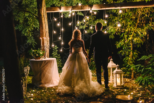 Photo Night wedding ceremony with candles, lanterns and lamps on tree