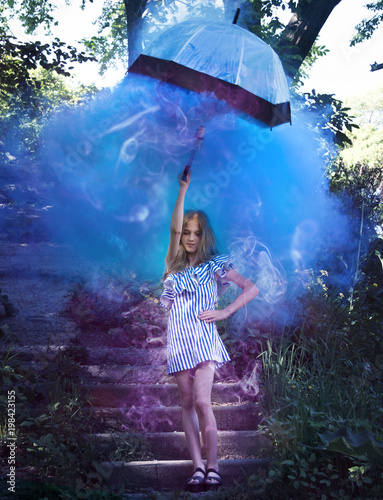 La pose en embrasure Forets enfants young girl with umbrella in hand, on the stairs, which meets the bright, blue smoke.