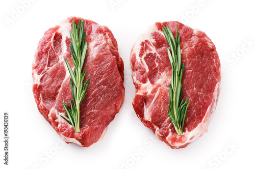 Fresh raw pork steaks and rosemary isolated on white background.