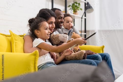 Cuadros en Lienzo beautiful young family watching tv together on couch