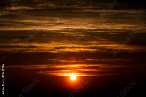 Photo sur Toile Rouge mauve amazing sun at dusk clouds. sunset image. beautiful red cloudy sunset in orange sky, dramatic view. fascinating wallpaper. beautiful nature moments, breathtaking scenery. pure beauty