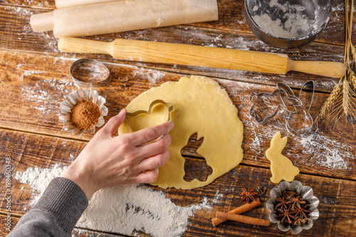 Fototapety, obrazy: Dough for baking curly cookies on a wooden table and hand holding a mold. .