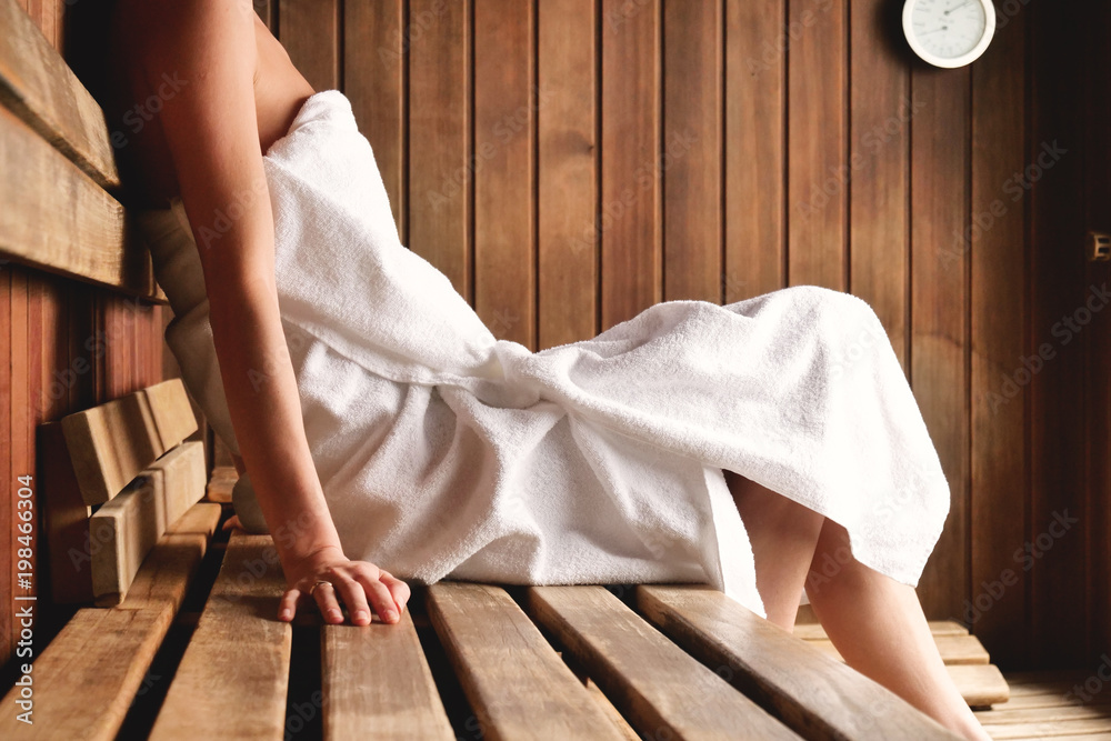 Fototapeta A beautiful woman wearing a white towel takes a sauna: The sauna is made of wood with a large window with a view of the snow. Concept of: relax, vacation, wellness center.
