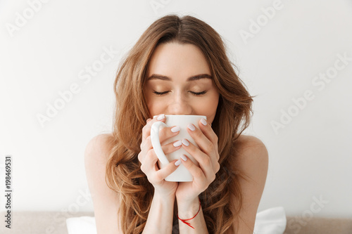 Poster The Portrait of lovely woman with beautiful brown hair drinking morning coffee or tea, while resting in bed
