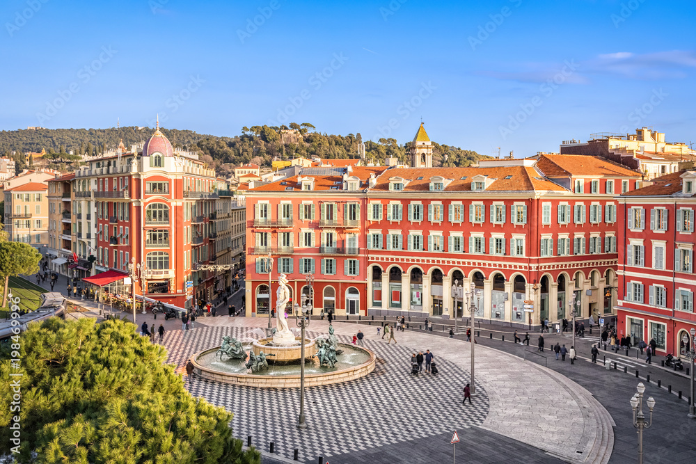 Fototapeta Aerial view of Place Massena square with red buildings and fountain in Nice, France
