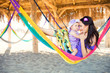happy stylish family with cute daughter relaxing in hammock on summer vacation in evening sun light on the beach. hipster couple with child resting and having fun in sunset.
