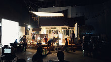 Silhouette Group Of People Working In Big Production Studio For Shooting Or Filming TV Commercial With Highly Quality Digital Video Camera And Professional Lighting Set And Prop.
