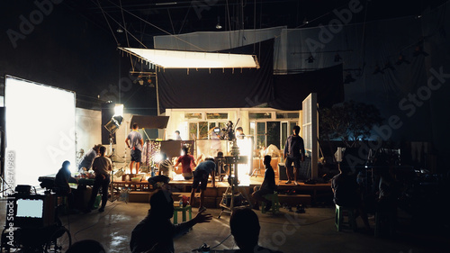 Photo  Silhouette group of people working in big production studio for shooting or filming TV commercial with highly quality digital video camera and professional lighting set and prop