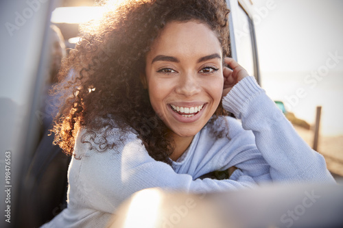 Fotografie, Obraz  Young woman leaning on open window of car looking to camera