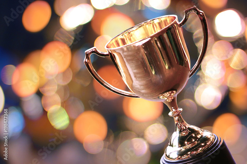Fotografia, Obraz  Winner hold trophy with abstract bokeh light background