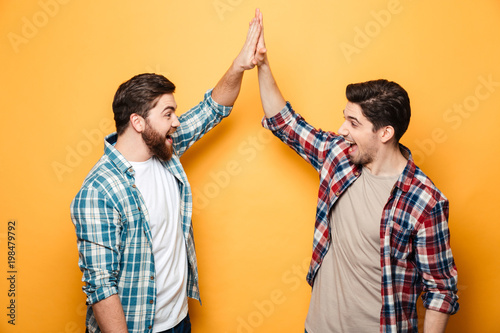 Valokuva  Portrait of a two happy young men giving high five