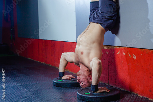 Photo of a young fit man doing a handstand exercise at a cross fit gym Wallpaper Mural