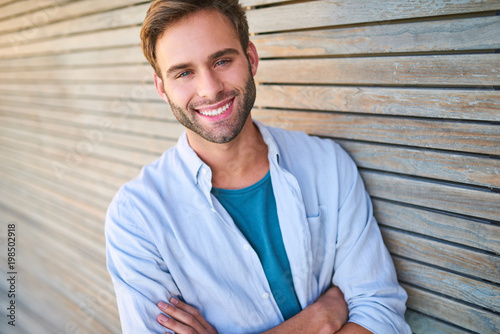 Fotografía  Tightly cropped image of handsome young male in his mid 20s smiling at camera with his teeth showing and his arms crossed while leaning against beautiful wooden cladding outdoors