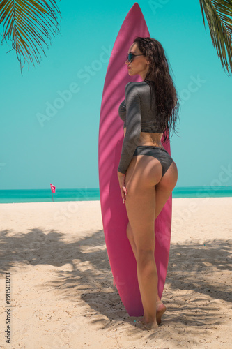 Back view of beautiful young woman in swimsuit and sunglasses posing with pink s Poster