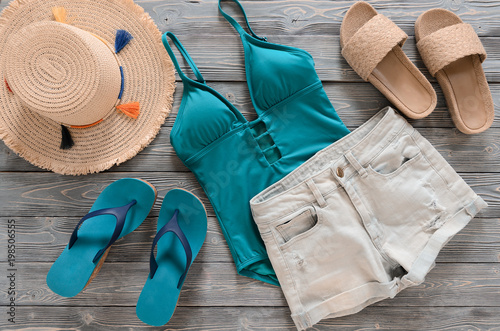 Obraz Womens clothing, accessories (denim shorts, straw hat, swimsuit, sandals) on grey wooden background. Trendy fashion outfit. Shopping, travel, summer, beach concept, abstract.  Flat lay - fototapety do salonu