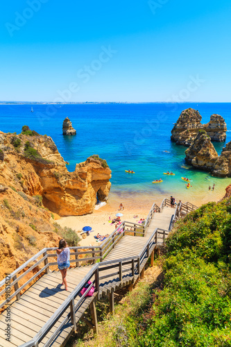 Unidentified young woman tourist taking photo of Praia do Camilo beach from wooden steps, Algarve region, Portugal