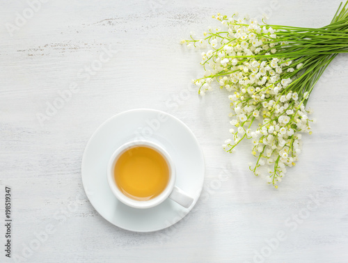 Tuinposter Lelietje van dalen Cup of tea and bouquet of Lilies of the Valley on white rustic table.