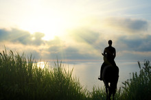 Silhouette Of The Rider Against The Sunset Sky.
