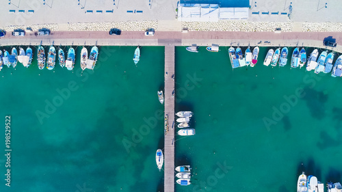 Foto op Canvas Cyprus Aerial bird's eye view of Zygi fishing village port, Larnaca, Cyprus. Bird eye view of aligned fish boats moored in the harbour, docked yachts, pier, wave breaker rocks near Limassol from above.