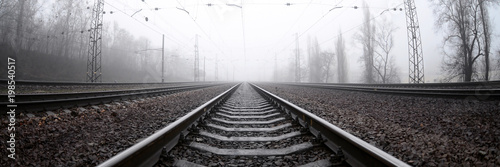 The railway track in a misty morning. A lot of rails and sleepers go into the misty horizon. Fisheye photo with increased distortion