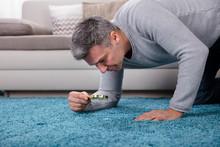 Man Looking At Carpet Through ...