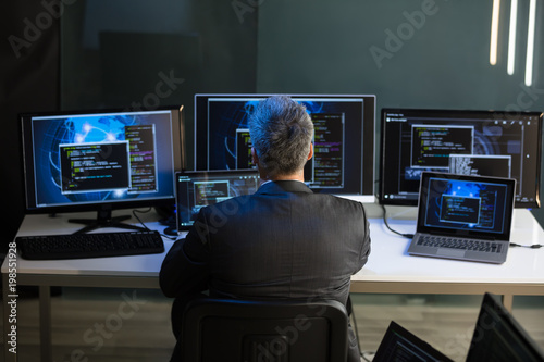 Fotografie, Obraz  Businessman Looking At Multiple Computer Screens