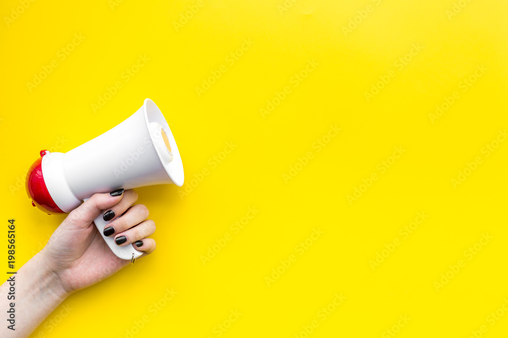 Fototapeta Megaphone make an announcement on yellow background top view copy space