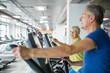 Happy senior woman training on stair stepper at gym