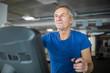 Happy senior man exercising on stair stepper at gym