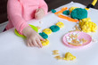 A 1.5 year old girl sits at a table and plays with a colored dough, on the table lie tools, molds and pasta for decor