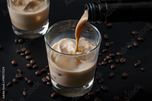 Keuken foto achterwand Cocktail Pouring irish cream in a glass with ice, surrounded by coffee beans on a dark black background