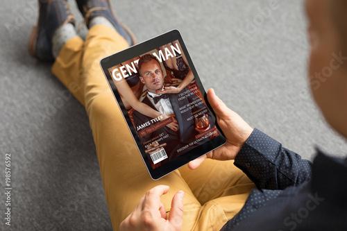 Man reading magazine on tablet