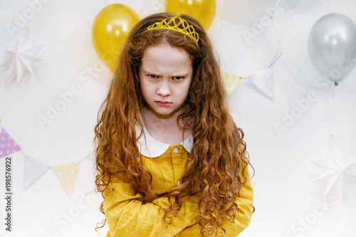 Valokuva  Emotional princess girl with angry expression on face in birthday party