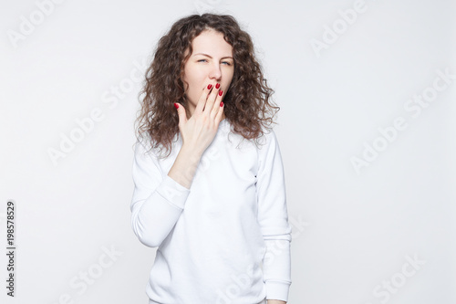 Vászonkép  Portrait of attractive young curly headed woman covering mouth with hand, keepin
