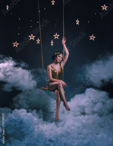 Fotografie, Obraz  An asterisk girl, swinging on a rocker in the clouds, among the stars and the night sky