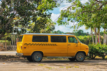 Picture Of Yellow Classic Taxi Van Between Green Trees