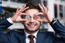 Smiling Young Businessman Covering Eyes With Bitcoins At Cryptocurrency Mining Farm