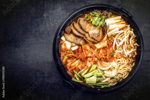 Traditional Korean kimchi jjigae with grilled pork belly and ramen as top view in a pot with copy space left