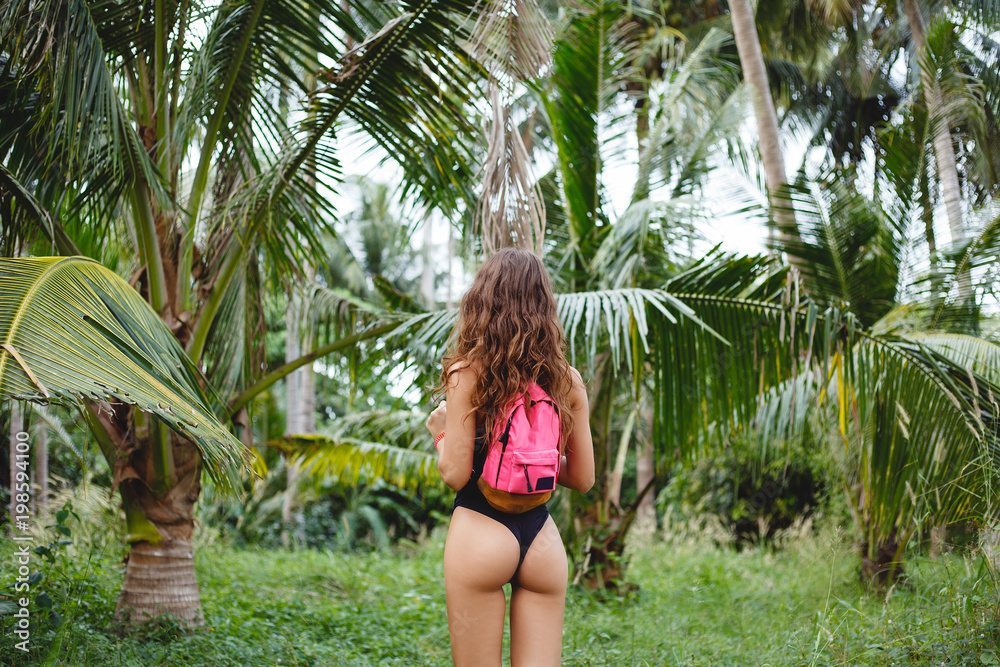 Fototapeta rear view of slim girl with backpack posing on tropical resort with palm trees