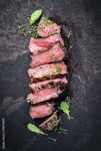 Garden Poster Steakhouse Barbecue wagyu point steak slices with lettuce and herbs as top view on a board with copy space