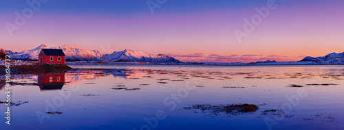 Deurstickers Ochtendgloren Landscape with beautiful winter lake, red rorbu house and snowy mountains at sunset at Lofoten Islands in Northern Norway. Panoramic view